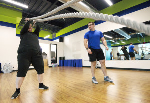 Laina Harris performs a resistance workout as fitness trainer Cody Sorensen gives instruction during