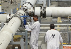 """Workers wearing protective clothing and footwear inspect a valve at the """"C"""" tank f"""