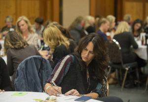 Janna Moats writes a check Monday to nonprofit Friends of the Children during the first meeting of 1