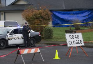 Officer Rudy Podhora keeps watch at the scene of a possible homicide in Woodland on Tuesday morning.