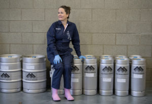 Teri Fahrendorf, malt innovation center manager for Great Western Malting Co., rests on kegs at the