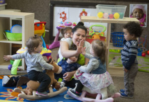 Teacher Linda Martinez shares a high-five while working with toddlers at Children's Village