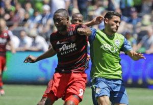 Portland Timbers forward Fanendo Adi, left, is challenged by Seattle Sounders midfielder Cristian Ro