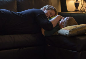 Erin Maher rests on her son Liam's chest as they play together in their apartment on Sept. 11,