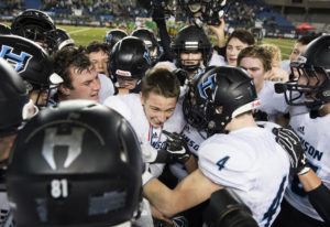 Hockinson surrounds quarterback Canon Racanelli as they celebrate their win against Tumwater after t