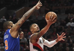 Portland's Damian Lillard drives to the basket on New York Knicks center Kyle O'Quinn during the sec