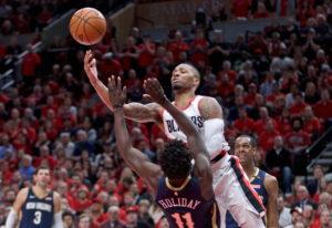 Portland Trail Blazers guard Damian Lillard shoots over New Orleans Pelicans guard Jrue Holiday duri