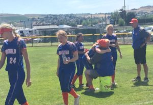 Ridgefield softball players hug coach Dusty Anchors after the team's season ended Saturday at t