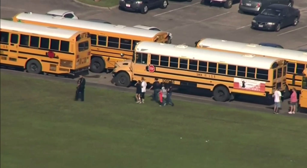 In this image taken from video a police officer walks near school buses as  law enforcement officers respond to a high school near Houston after an  active ...