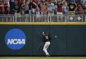 Oregon State right fielder Trevor Larnach (11) hits the wall on a double by Arkansas' Dominic Fletch