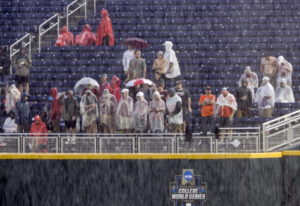 Spectators wait in the rain during a rain delay before Game 1 of the NCAA College World Series baseb