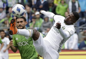 Portland Timbers midfielder Dairon Asprilla, right, kicks the ball in front of Seattle Sounders midf