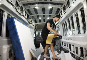 Brandon Anderson, a builder at Van Haus Conversions, starts the initial work of customizing a van at