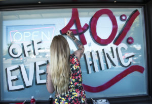 Jessie Leonetti, a budtender at Sticky's Pot Shop, paints a sale announcement on the store's window.
