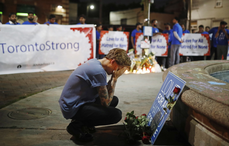 A man reacts at a vigil in remembrance of the victims of a shooting the evening before in Toronto on Monday