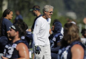 Seattle Seahawks head coach Pete Carroll smiles and he greets players at NFL football training camp,