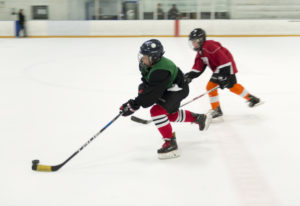 Max Gudanis, 10, sprints toward the goal, with Trenton Dodd, 11, in pursuit during a pickup hockey g
