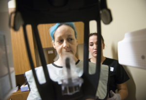 Timberly Eyssen, left, prepares for dental assistant Sam Mattix to take an X-ray of her teeth July 1