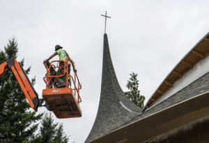 A contractor working at Vancouver United Church of Christ prepares to install new windows on July 19
