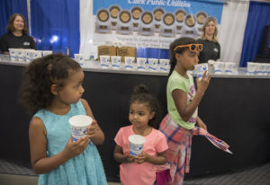 Janaye Bol, 6, of Graham, left in blue, escapes from the heat with a cold cup of water with her sist