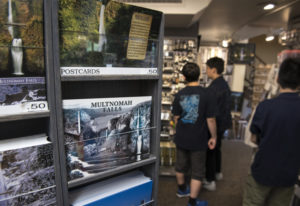 Visitors to the Multnomah Falls Lodge in Oregon look through the gift shop, which sustained heavy sm