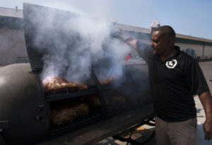 Donnie Vercher, owner of Daddy D's Southern Style BBQ, checks on brisket and pulled pork he's smokin