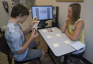 Jack Bellamy, 15, of Ridgefield, left, uses sequencing cards during cognitive therapy with speech la