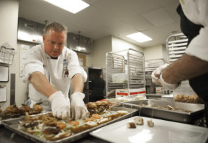 Executive chef Troy Lucio prepares miniature pub burgers before the ribbon-cutting ceremony at the H