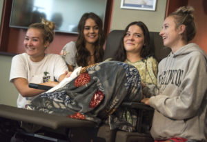 Jordan Holgerson, in chair, is surrounded by friends and family while joking with the media about he