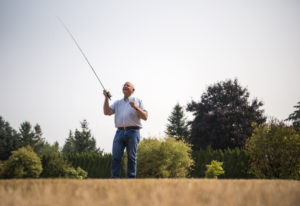 Mike McCoy, owner of Snake Brand Products, demonstrates fly-casting techniques on the lawn outside h