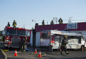 Firefighters work at the scene of a blaze at Vick's Market at 4903 East Fourth Plain Boulevard