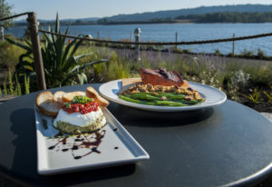 The Goat Cheese Torta, left, and the Potlatch Cedar Plank Salmon are seen here on the riverside pati
