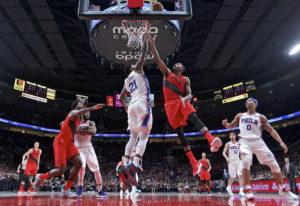 Portland Trail Blazers forward Maurice Harkless, center right, shoots over Philadelphia 76ers center
