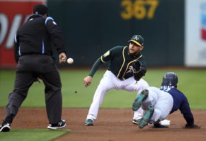 Oakland Athletics' Jed Lowrie waits for the ball to tag out Seattle Mariners' Jean Segura,