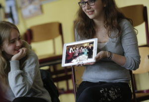 Jewish teenager Sophie Steiert, right, shows a picture of Jewish daily life on a tablet computer Jun