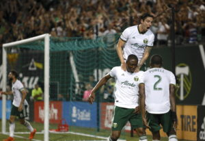 Portland Timbers' Fanendo Adi, second from right, celebrates with teammates after scoring a goal. A