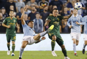 Sporting Kansas City defender Roger Espinoza, front left, clears the ball away from Portland Timbers