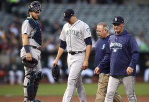 Seattle Mariners pitcher James Paxton, second from left, is escorted off the field after being hit b