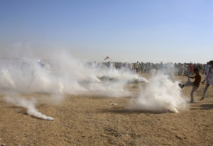 A protester tries to kick back a teargas canister fired by Israeli troops Friday near the southern G