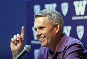 Washington NCAA college head football coach Chris Petersen points skyward in response to hearing Blu