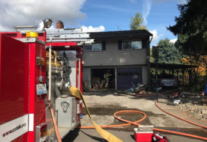 Vancouver Fire Department and Clark County Fire District 6 firefighters root through a garage in the