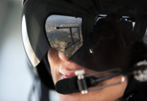 The view is reflected in the visor of flight nurse Michelle LaVina during a demonstration flight in