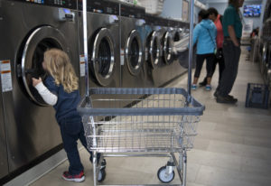 Leo Guerra, 3, peeks in the washer before helping his parents unload laundry at Cedars Laundromat in