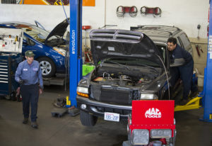 Left: Butch Brawner of Hoesly Eco Automotive, left, and colleague Fernando Sanchez work on cars for