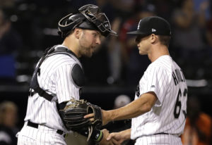 Chicago White Sox relief pitcher Ian Hamilton, right, celebrates with catcher Kevan Smith after the
