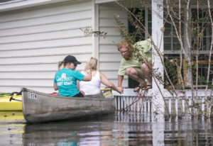 David Covington jumps from a porch railing to his canoe along with Maura Walbourne and her sister Ka