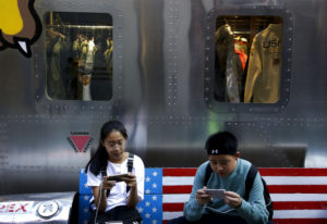 Shoppers sit on a bench with a decorated with U.S. flag browsing their smartphones outside a fashion