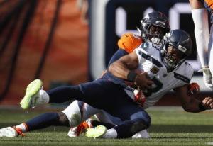Denver Broncos linebacker Von Miller, behind, hauls down Seattle Seahawks quarterback Russell Wilson
