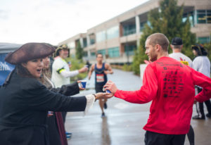 Sherry Honea, left, hands out water to runners while dressed as a pirate during the inaugural Apple