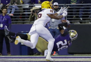 Washington wide receiver Ty Jones falls backward as he catches a pass for a touchdown, while Arizona